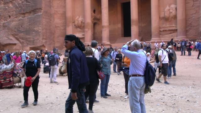 vídeos de stock e filmes b-roll de tourist crowds in front of  al khazneh, or the treasury, petra in jordan - petra