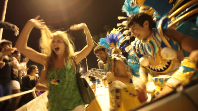 tourist dances with costumed carnivale performers sparkle and dance in argentina mardi gras parade - mardi gras stock videos and b-roll footage