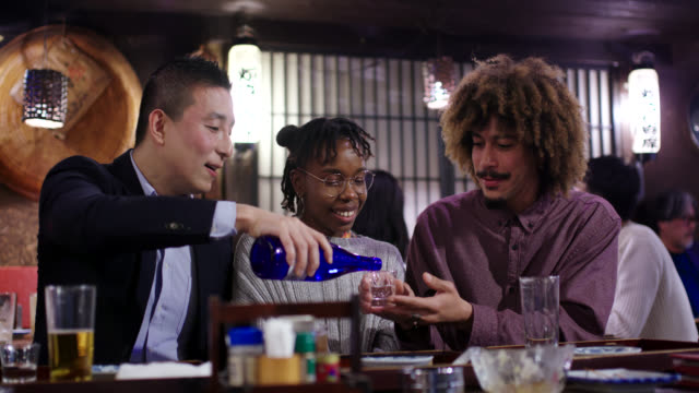 tourist drinking sake with locals in a traditional japanese izakaya - tourist stock videos & royalty-free footage