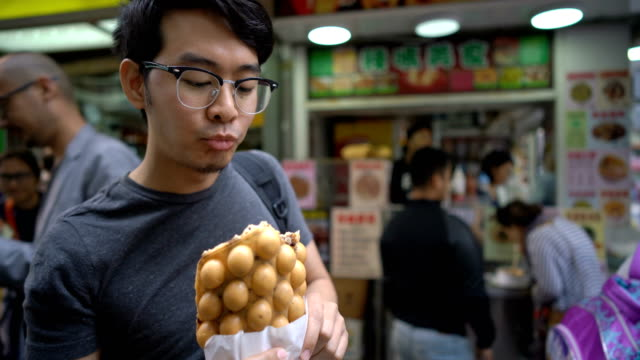 tourist eating hong kong signature snack egg waffles/bubble waffles - waffles stock videos and b-roll footage