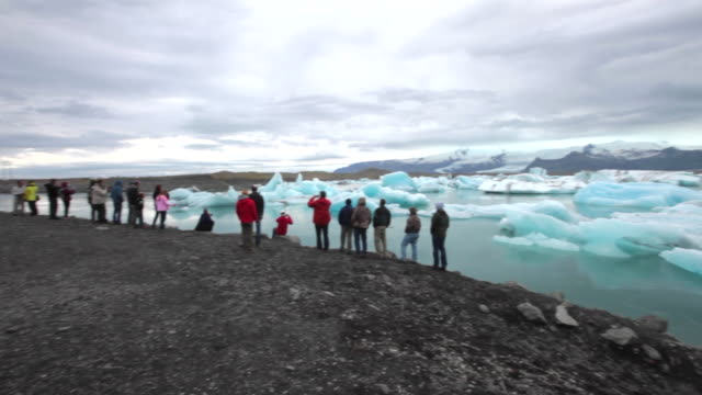vidéos et rushes de tourist enjoying the floating icebergs on the jökulsárlón glacier lagoon in south iceland - plan large