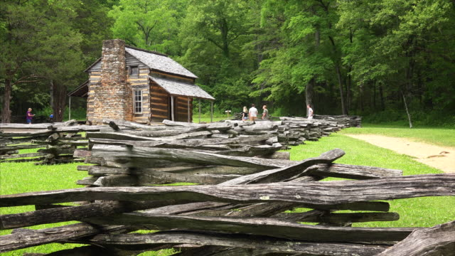 tourist explore the john oliver log cabin in the great smoky mountains national park, tennessee - 山小屋点の映像素材/bロール