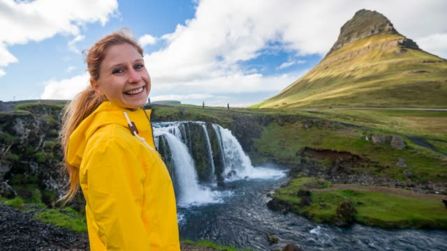 Tourist exploring Iceland, admiring Kirkjufell mountain and Kirkjufellsfoss waterfall