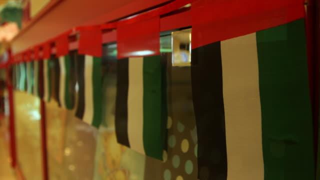 vidéos et rushes de tourist gift shop, abu dhabi. rack-focus on emirati flag bunting hung in a gift shop. - banderole signalisation