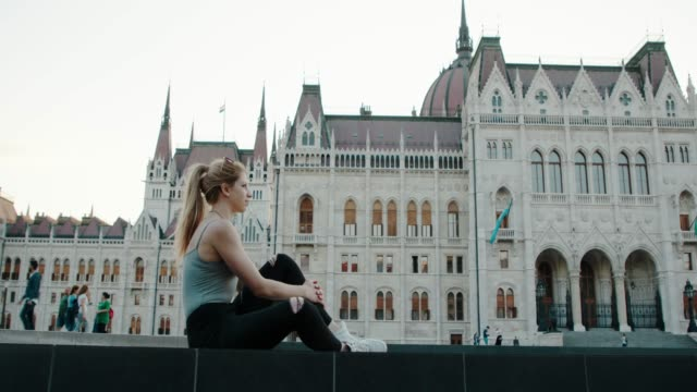 tourist girl sitting in front of budapest parliament - royal palace of buda stock videos & royalty-free footage