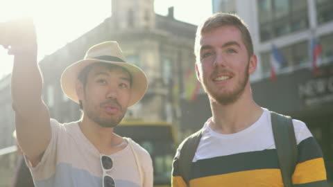 vidéos et rushes de guide touristique parlant à son client pendant la promenade de ville - montrer la voie