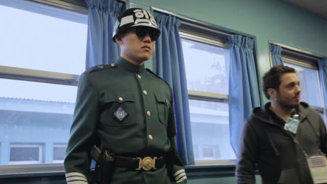 MS A tourist has his photograph taken next to a border guard in UN buildings of the DMZ / Panmunjom, Korea
