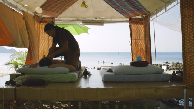 vidéos et rushes de tourist having a massage in a massage parlour on the beach in thailand - massage