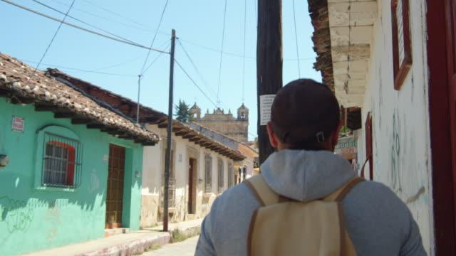 vídeos y material grabado en eventos de stock de tourist in a hoodie walking down a street at a village in san cristobal de las casas, chiapas, mexico - pared de cemento