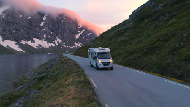 tourist in camper van moving along mountain and fjord during sunset - geiranger fjord, norway - 沿岸点の映像素材/bロール