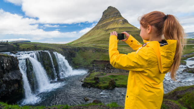 Tourist in Iceland taking pictures of Kirkjufellsfoss waterfall