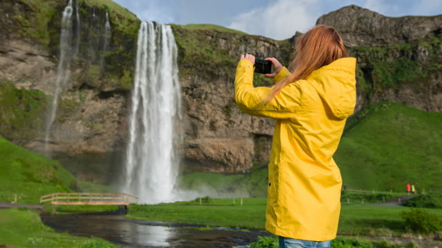 tourist in iceland taking pictures of seljalandsfoss waterfall - seljalandsfoss waterfall stock videos and b-roll footage