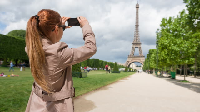 Tourist in Paris photographing Eiffel Tower with smartphone