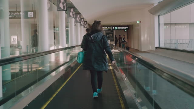 tourist in walkway escalator with backpack. - jacket stock videos & royalty-free footage