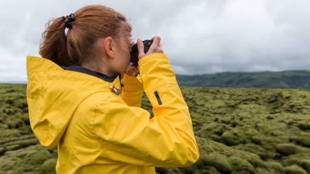Tourist in yellow raincoat photographing green and mossy landscape of Iceland