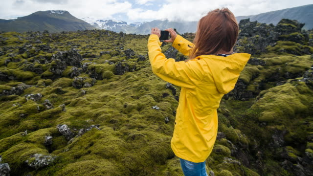 tourist in yellow raincoat photographing moss cover on volcanic landscape of iceland - natural landmark stock videos & royalty-free footage