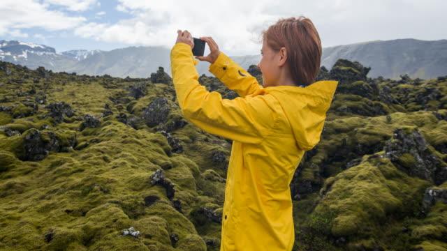 vídeos de stock e filmes b-roll de tourist in yellow raincoat photographing moss cover on volcanic landscape of iceland - explorador