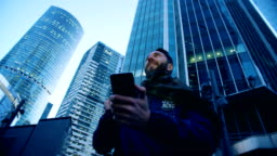 Tourist is operating his smartphone while being next to skyscrapers. Epic cinema camera shot.