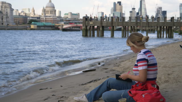 Tourist is sitting on embankment beach at river Thames,writing in diary.