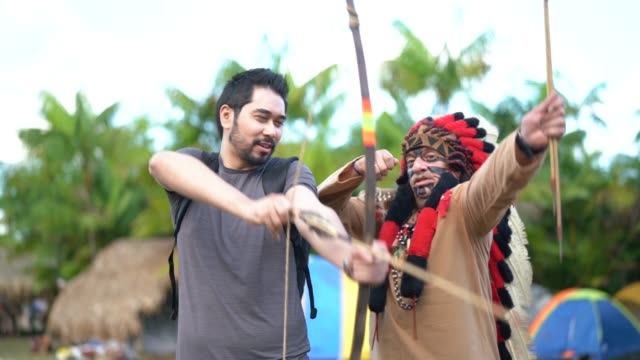 tourist learning lessons, from tupi guarani tribe indigenous, with bow and arrow, brazil - america latina video stock e b–roll