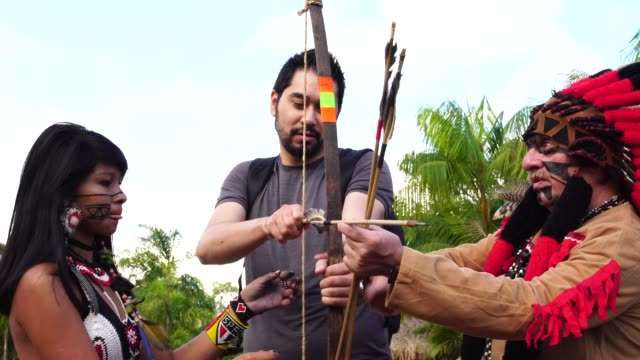 tourist learning lessons, from tupi guarani tribe indigenous, with bow and arrow, brazil - history stock videos & royalty-free footage