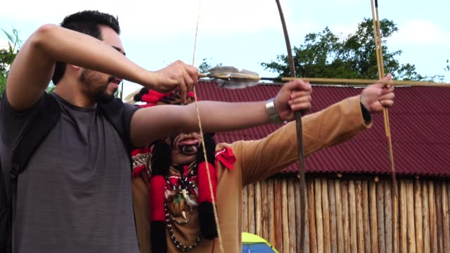 tourist learning lessons, from tupi guarani tribe indigenous, with bow and arrow, brazil - manaus stock videos and b-roll footage