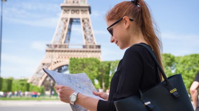 touristischer stadtplan paris betrachten und sich dann auf den eiffel-turm - hoch position stock-videos und b-roll-filmmaterial
