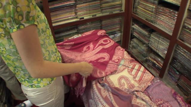 ms td tourist looking at scarves in silk store, mumbai, india - 陳列ケース点の映像素材/bロール