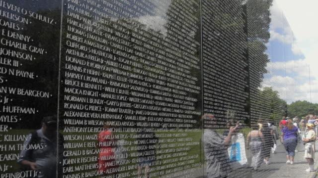 MS PAN Tourist looking hero names of war dead at vietnam veterans memorial wall monument / Washington DC, Washington District of Columbia, United States