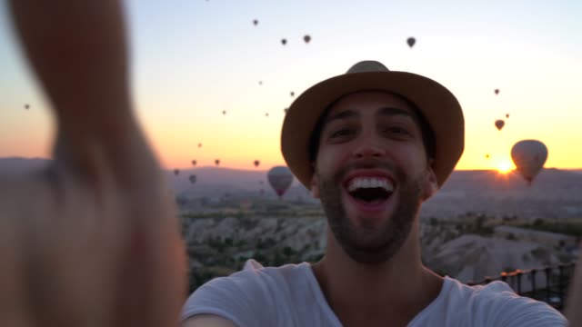 tourist man taking a selfie on cappadocia, turkey - progress stock videos & royalty-free footage