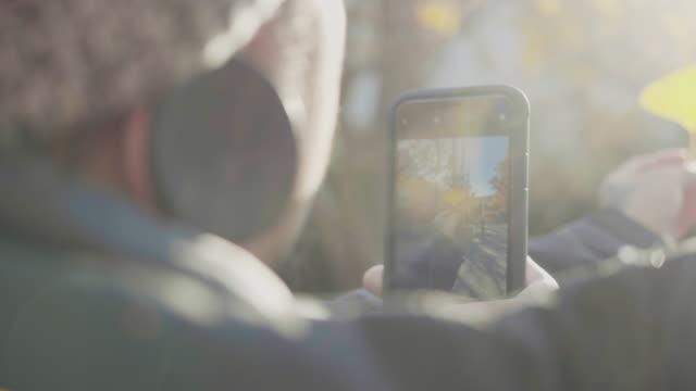 vídeos y material grabado en eventos de stock de hombre turista tomando selfie en el parque de otoño en tokio - photographing