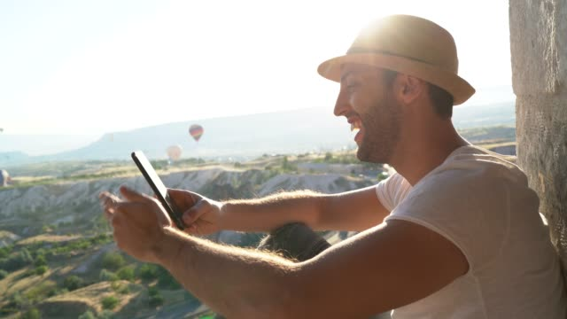 tourist man using mobile and looking at view during ballooning festival, cappadocia, turkey - unesco world heritage site stock videos & royalty-free footage