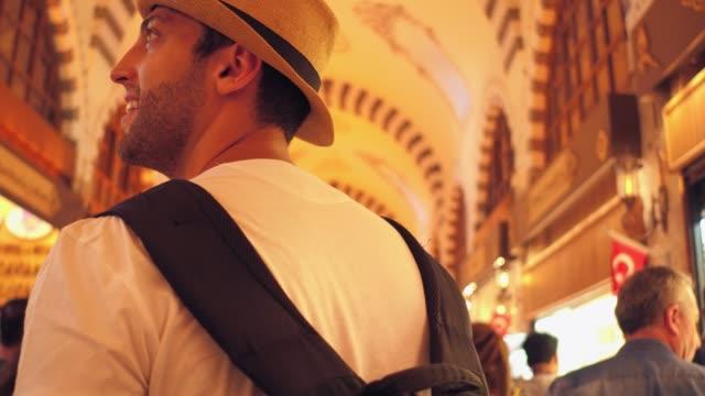 stockvideo's en b-roll-footage met toeristische man wandelen en ontdekken istambul markt, turkije - grote bazaar van istanboel istanboel