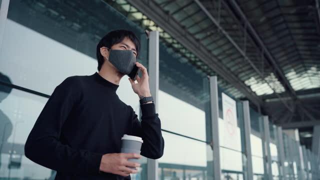 vídeos y material grabado en eventos de stock de hombre turístico usar máscara facial usando el teléfono mientras espera - neumonía