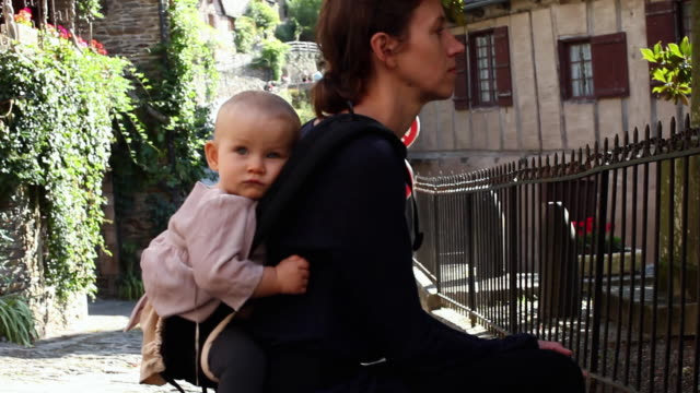 vídeos y material grabado en eventos de stock de ms tourist mother resting with baby girl (6-11 months) on her back / estaing, france - 6 11 meses