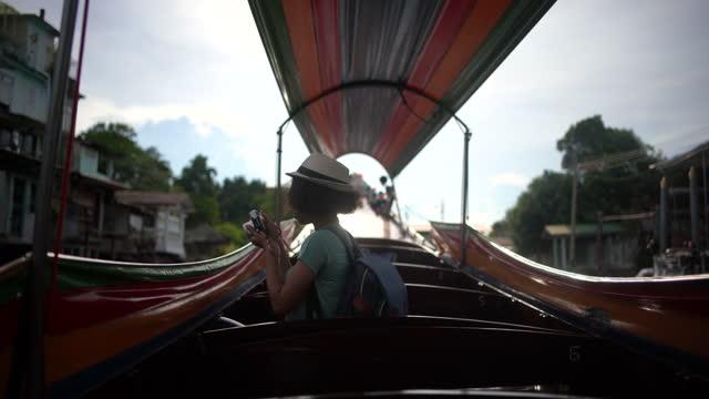 vidéos et rushes de tourist on a romantic sunset cruise on a river in bangkok, thailand. - une seule femme d'âge mûr