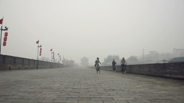 ws la pan ts tourist on ancient city wall on foggy day/xian,shaanxi,china - 史跡めぐり点の映像素材/bロール