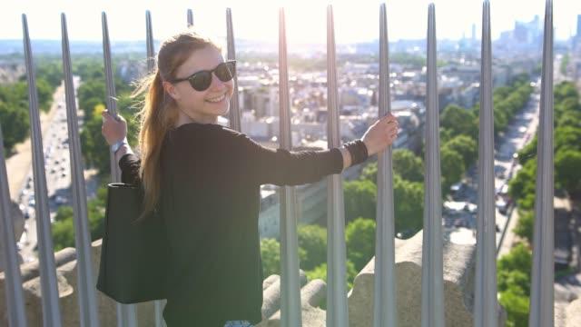 vídeos de stock, filmes e b-roll de turista no topo do arco do triunfo em paris com vista para a cidade, sorrindo para a câmera em um dia ensolarado - ponto de observação
