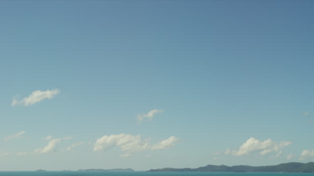 Tourist on Whitehaven Beach with downward pan.