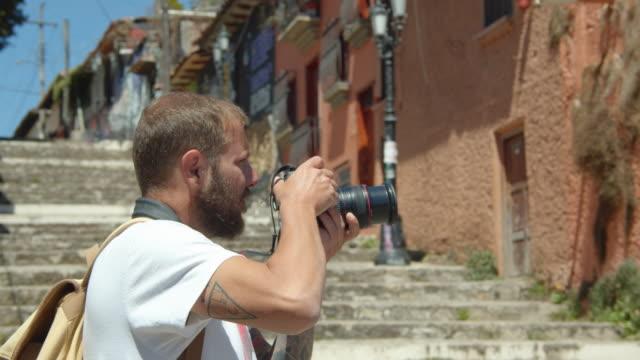 vídeos y material grabado en eventos de stock de tourist photo-walking around a neighborhood in san cristobal de las casas, chiapas, mexico - pared de cemento