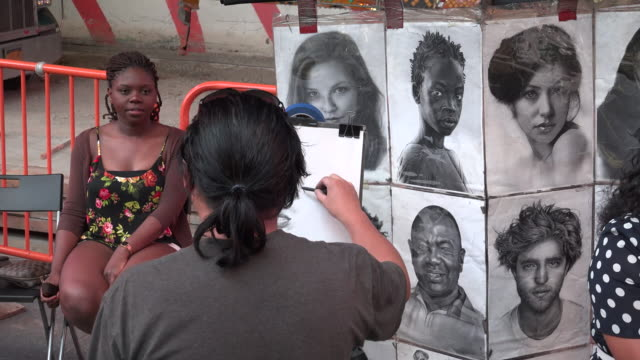 Tourist pose for a hand drawn portrait sketch in Times Square by of the many portrait artist / Times Square Midtown Manhattan Broadway and Seventh...