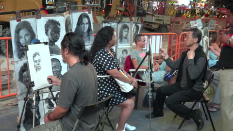 vídeos y material grabado en eventos de stock de tourist pose for a hand drawn portrait sketch in times square by of the many portrait artist / times square, midtown manhattan, broadway and seventh... - 7th avenue