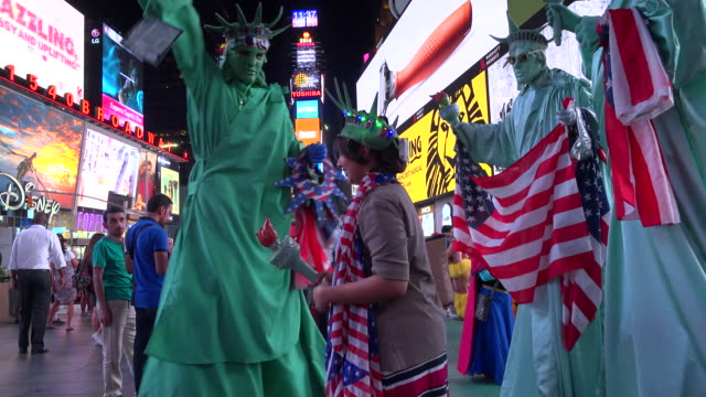 Tourist pose for a photograph with the Times Square street performers / Times Square Midtown Manhattan Broadway and Seventh Avenue 7th Avenue New...