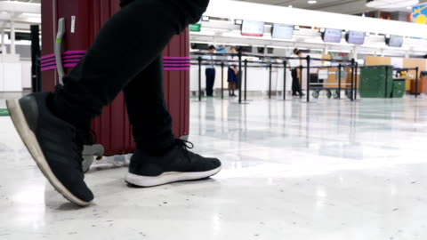 slo mo - a tourist pulling his luggage in an airport - gate stock videos & royalty-free footage