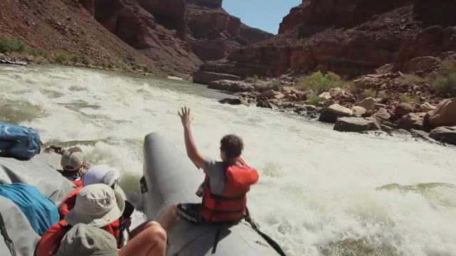 WS POV Tourist rafting on river Colorado in Grand Canyon with water splashing on them / Grand Canyon Village, Arizona, USA