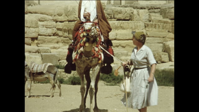 A tourist rides a camel in Giza,