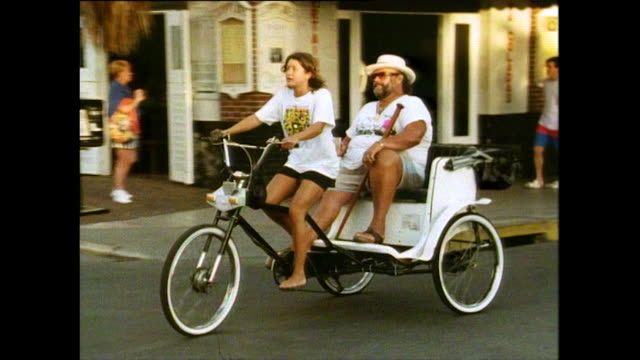 vídeos de stock, filmes e b-roll de tourist rides in cycle rickshaw in key west, 1991 - jinriquixá puxado por bicicleta