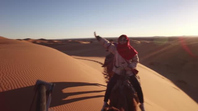 tourist riding camel train in sahara desert, africa - camel stock videos & royalty-free footage