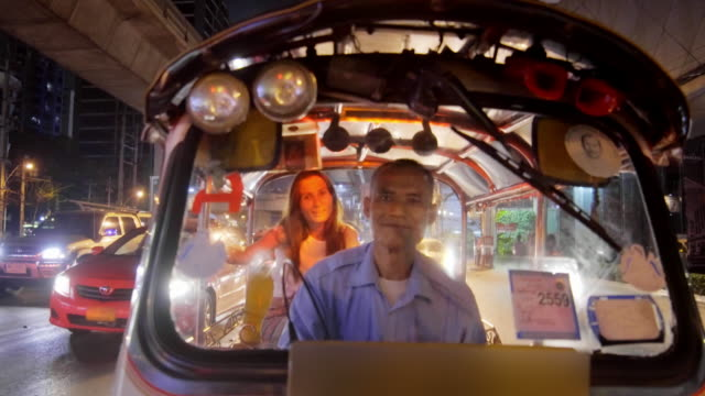 tourist riding tuk tuk in bangkok 4k - risciò video stock e b–roll