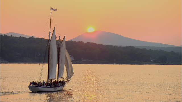 stockvideo's en b-roll-footage met low aerial, tourist sailboat entering bay at sunset, camden, maine, usa - maine